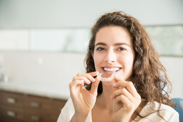 (SMALL) Young woman smiling and holding her Invisalign clear aligners